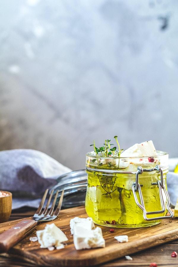 Fetaost marinert i olivenolje med friske urter i glasskrukke. Trebakgrunn.