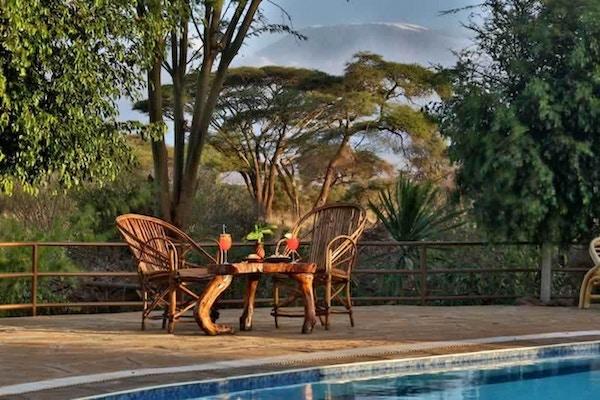 to stoler og et trebord med drikke ved bassenget