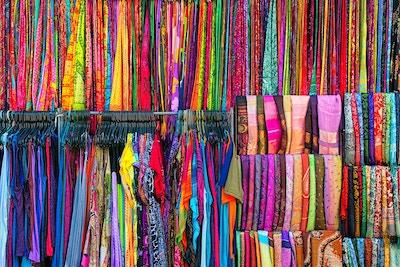 Fargerike klesstoffer og saronger på Ubud-markedet, hengt opp slik at kundene kan bla gjennom.