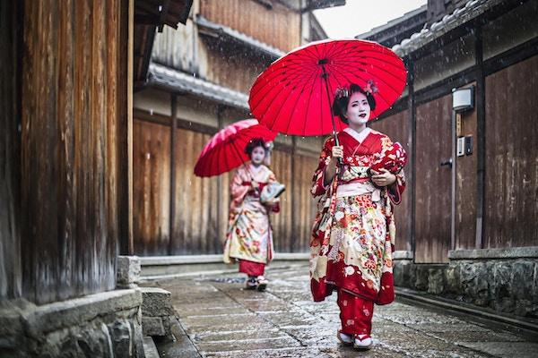 Maikos som går på en regnfull dag i gatene i Gion, Kyoto.