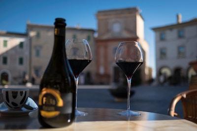 to glass rødvin på et bord med sentrum i bakgrunnen