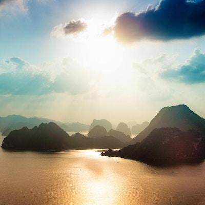 Halong Bay Vietnam luftfoto ved solnedgang som viser de karakteristiske øyene som er dekket av jungelen.