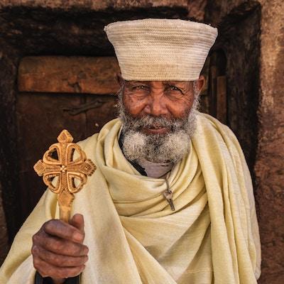 Katolsk prest som står foran en av steinhugges kirker i Lalibela. Etiopia, Øst-Afrika