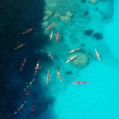 En gruppe kajakkpadlere er samlet på det blå havet utenfor Kefalonia