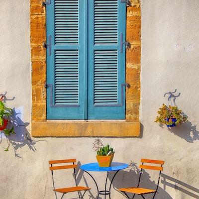 Blå skoddervindu og vakre små stoler og et bord på fortauet på Kypros