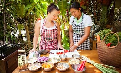 To kvinner som kutter grønnsaker blant frodige palmer