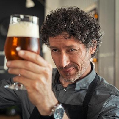 Mann som undersøker kvaliteten på håndverksøl på bryggeriet. Inspektør som jobber på alkoholproduserende fabrikk og sjekker øl.