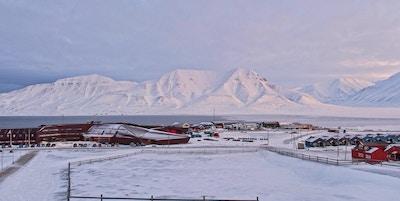 Vakker utsikt mot snødekte fjell på Svalbard