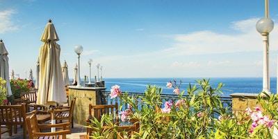 Terrasse med bord og stol. Utsikt mot Amalfis kyst