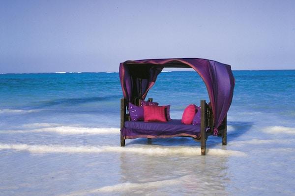 Sittemøbel ute i havet med Zanzibar med røde og lilla puter og overtrekk