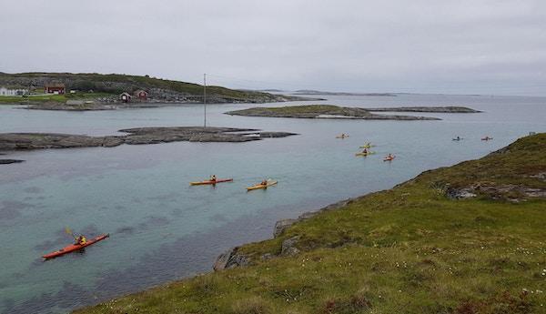 Mennesker sett ovenfra som padler langs kysten i klart vann med grå himmel