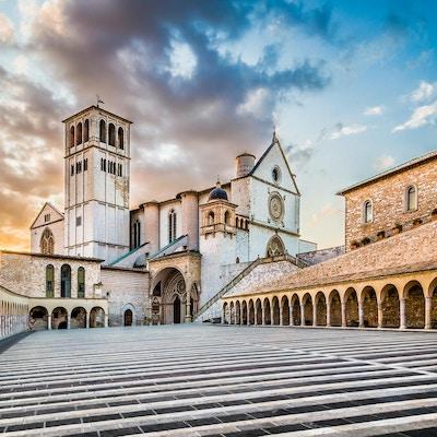 Berømte basilikaen St. Francis of Assisi (Basilica Papale di San Francesco) med Nedre Plaza ved solnedgang i Assisi, Umbria, Italia.