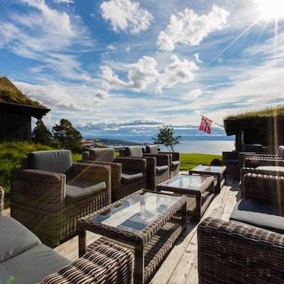 Hagemøbler ute på en terrasse med utsikt over fjord og fjell. Norsk flagg vaier