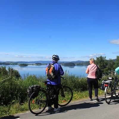Syklister med sekk som tar en pause og ser utover fjorden