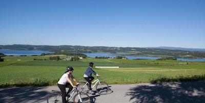 to syklister ute på tur med hjelm og fritidsklær. Utsikt over grønne sletter og vann