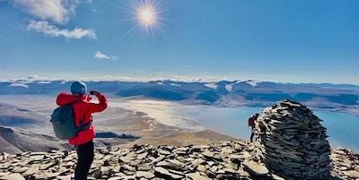 Kvinne som står og tar bilde med mobilen utover landskapet fra et fjell