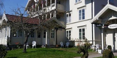 Stor hvit hotellbygning med stoler plassert utenfor og frukttrær i hage. Skilt med resepsjon