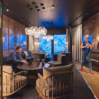 Avslappingsområde på hotell med dype lenestoler og mange lamper som henger fra taket