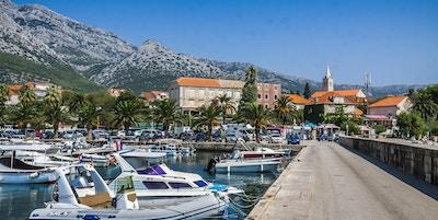 Havn med mange småbåter, palmer i bakgrunnen og hus derav en kirke