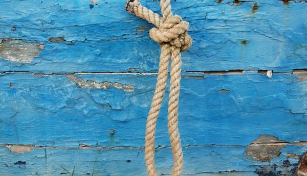 En vegg med slitt blå maling og et tau
