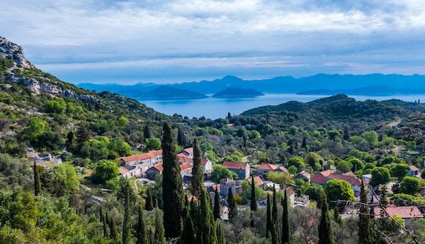 Øya Mljet i Kroatia - 4. mai 2015 - Liten landsby på øya Mljet, Kroatia, med Adriaterhavet og fjellene i bakgrunnen.