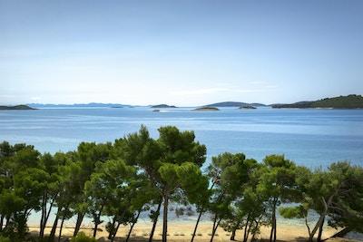 Strand, sand, trær og vann med øyer i horisonten