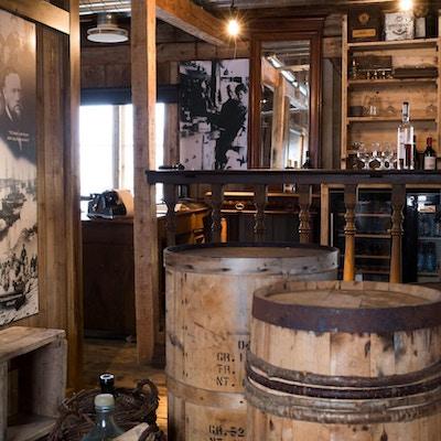 Tønner og gamle trehyller med svart hvitt plakater på veggene i et gammelt lokale som brukes til bar
