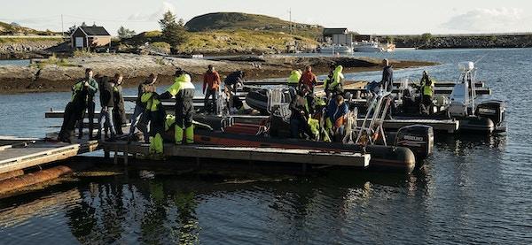 Flere personer i verneutstyr gjør seg klare til å sette av gårde i en RIB-båt på vannet
