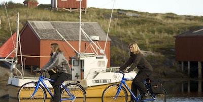 To kvinner som sykler langs vannet med båt og sjøhus i bakgrunnen