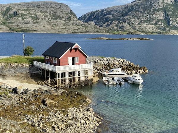 Rød hytte bygget på påler over vannet med båter rundt nede i vannkanten