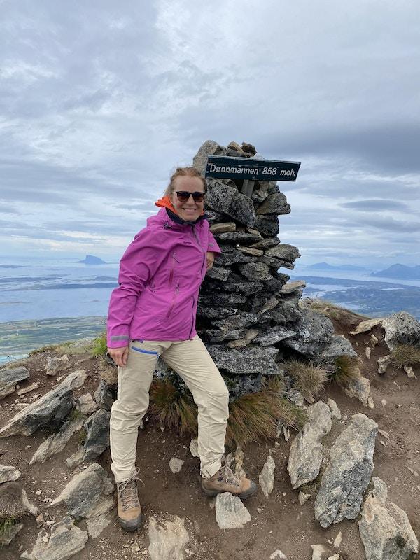 Kvinne i lilla jakke og turutstyr står på toppen av et fjell i Norge