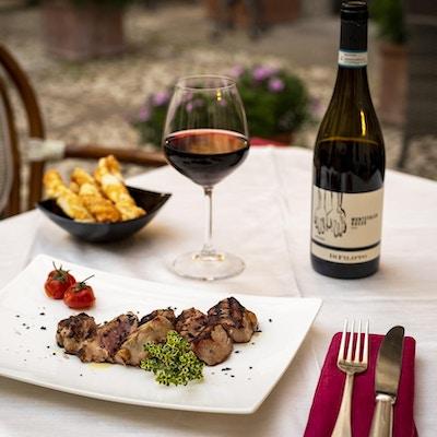 en hvit tallerken med grillet kjøtt og et glass vin til siden