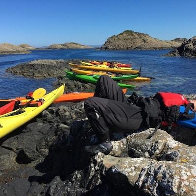 Flere kajakker i ulike farger er dratt på land mens en mannlig padler  ligger på et svaberg og slapper av i solen