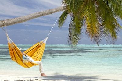En ung mann iført stråhatt slapper av i en oransje hengekøye som er hengt på et kokosnøttpalm. Den hvite sandstranden og fargen på vannet er turkis og er en idyllisk og unik beliggenhet på Maldivene.