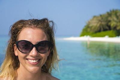 Portrett av en ung kvinnelig turist med solbriller, glad og smilende på en sandstrand med turkis vann, blå himmel og grønn vegetasjon i bakgrunnen. Bildet er tatt i Det indiske hav ikke langt fra Maafushi Island på Maldivene.