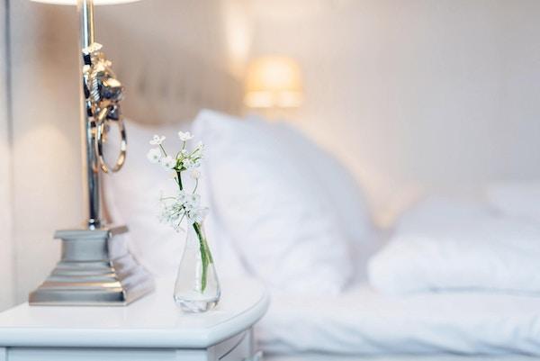 Detalj med blomster på nattbord med hotellseng i bakgrunnen.