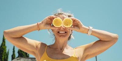 Voksen kvinne som står utendørs i sollyset. Hun holder to skiver sitroner og dekker øynene mens hun smiler.