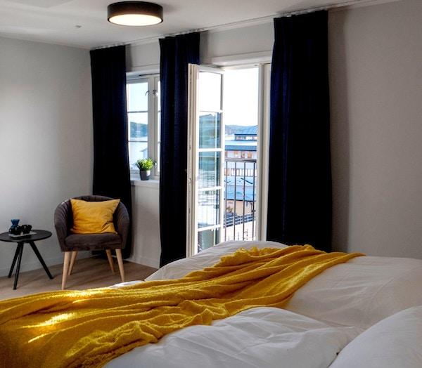 Hotellerom med seng, stol og vinduer med åpning mot fransk balkong