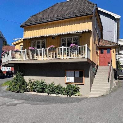 Bilde av gult hus med hvitt gelender, trapp og blomsterkasser på veranda