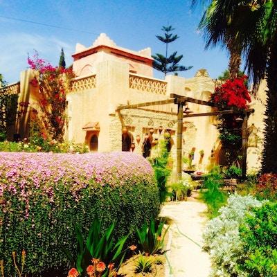 Gult murhus i solen med røde, rosa og lilla blomster ved siden av