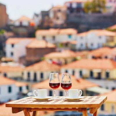 To glass Madeira-vin og to kopper fersk espressokaffe på kafé med utsikt til Funchal by, Madeira, Portugal