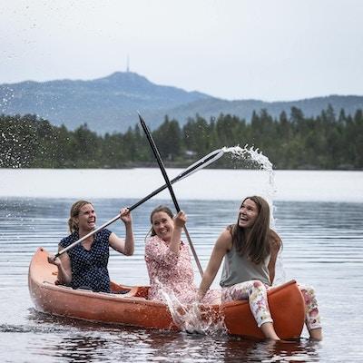 tre jenter ute i kano som spruter med åre og har det gøy