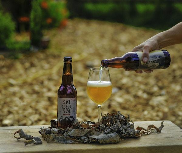 En ølflaske er plassert på en benk med bark rundt mens en hånd skjenker i et glass