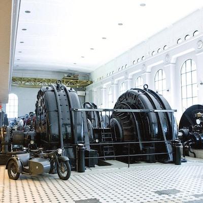 Gamle maskiner og en motorsykkel med sidevogn inne i en nedlagt fabrikkhall som nå er museum
