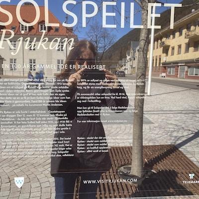 Et speil og tekst om solspeilet. Ei kvinne står og tar bilde foran det og speilbildet vises