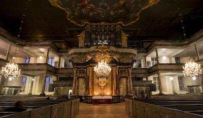 Altertavle og benker inne i en kirke vakkert opplyst med lysekroner