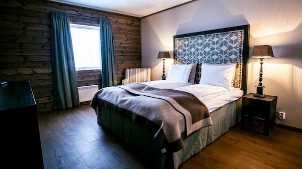 Hotellrom med vindu, gardiner ned til gulvet, tregulv og tekstiler i duse toner. Nattbord og lamper.