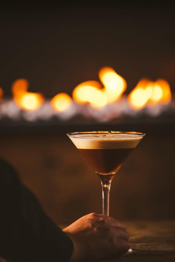 Et glass med drikke, brun med skumkant, holdes i hånden av en person
