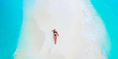 Vakker kvinne som ligger på sandbanken omgitt av turkis hav ovenfra