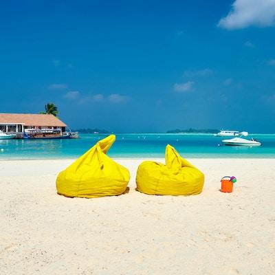 Tropisk strand med gule beanbag-stoler. Sommerferie på Maldivene.